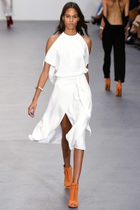 Silver jewellery and orange brown ankle boots and navy nail polish against this white dress really pop. From Issa