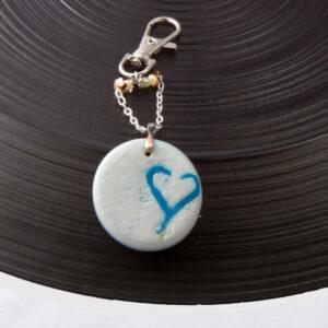 Blue Heart inlaid in pearl polymer clay circle. Handbag charm